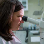 Female researcher looks into microscope in laboratory